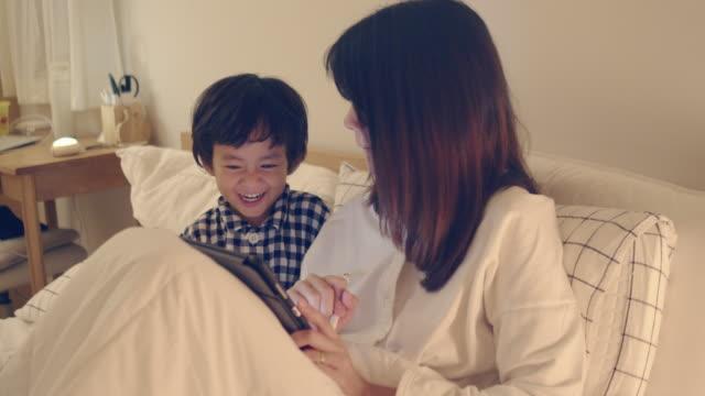 mor och son som arbetar hemma. - digital reading child bildbanksvideor och videomaterial från bakom kulisserna