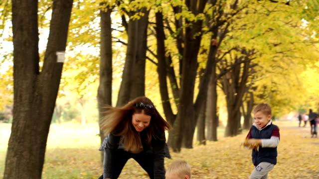 vídeos de stock e filmes b-roll de mother and sons playing with fallen leaves in autumn park. - passagem de ano
