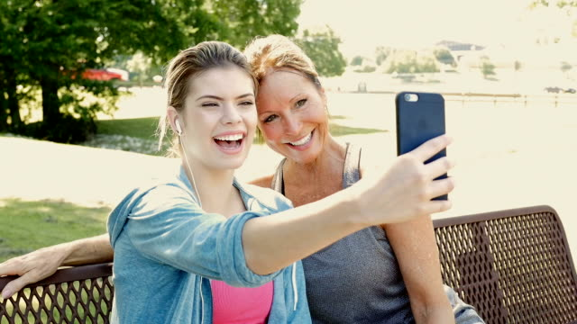 vídeos de stock e filmes b-roll de mother and teen daughter taking a selfie photo together outdoors at park - sorriso aberto