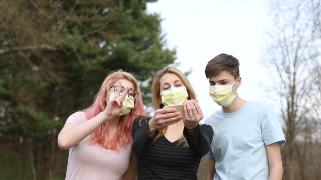 vidéos et rushes de mère et adolescents dans des masques de visage prenant des selfies - 18 19 ans