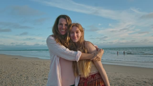 Mother and teenage daughter at beach hugging and smiling at camera video