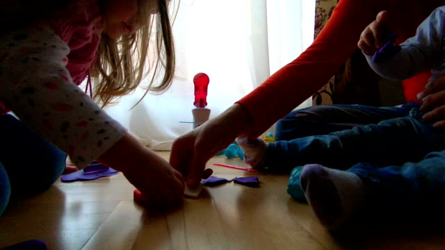 mother and three kids playing with plasticine - mika video stock e b–roll