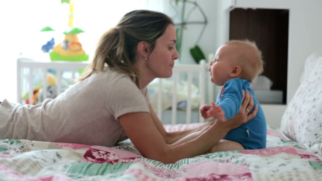 Mother and toddler child in bed, playing together, happiness family concept, kid and mom bonding