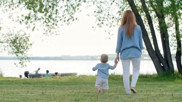 Bидео Mother and Toddler Watching Boat on Lake