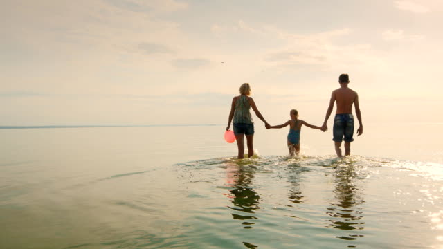 Mother and two children walking on the shallow water at sunset video