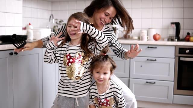vídeos y material grabado en eventos de stock de madre y sus dos hijas están bailando en la cocina - copiar
