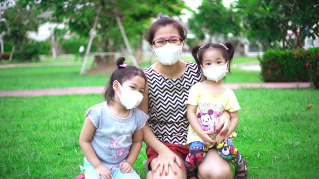 Mother and two daughters smiling behind a protective face mask in public park