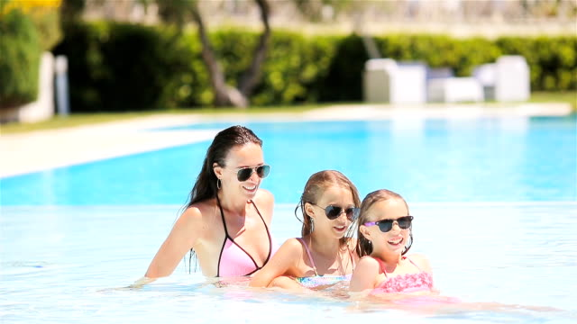 vídeos de stock e filmes b-roll de mother and two kids enjoying summer vacation in luxury swimming pool - mulher natureza flores e piscina