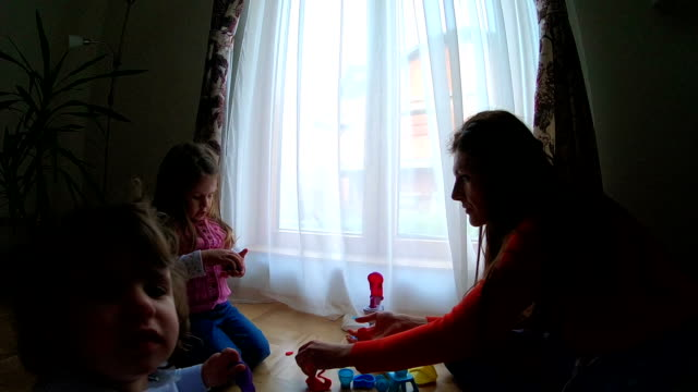 mother and two kids playing with plasticine - mika video stock e b–roll