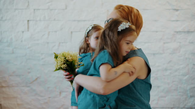 Mother and two little daughters are hugging each other video