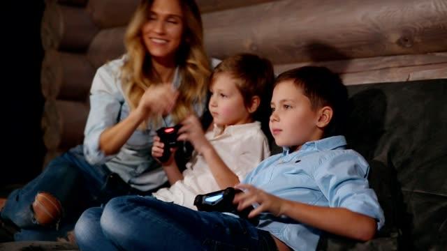 stockvideo's en b-roll-footage met moeder en twee zonen zittend op de bank in zijn huis spelen van videospellen met draadloze joystick. gelukkige mensen in het huis - sportwedstrijd