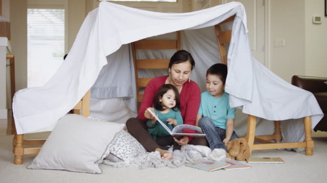 Mother and young children reading book in fort Mother and young children reading book in fort made of sheets and chairs indian family stock videos & royalty-free footage