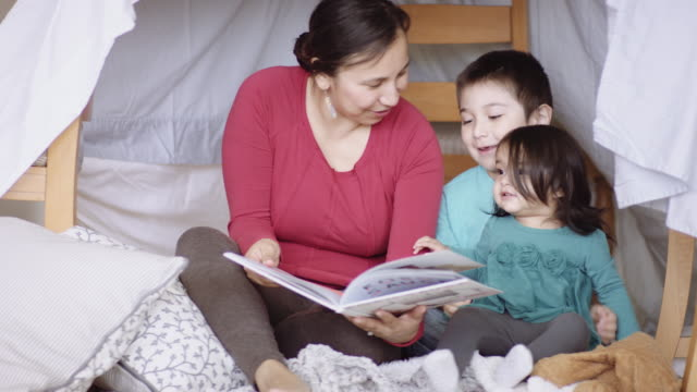 Mother and young children reading book in fort video