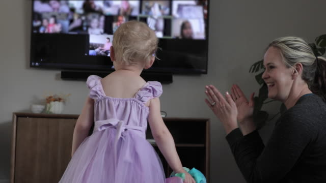 Mother and young daughter celebrate virtual birthday party In front of computer/TV screen, indoors mid adult stock videos & royalty-free footage