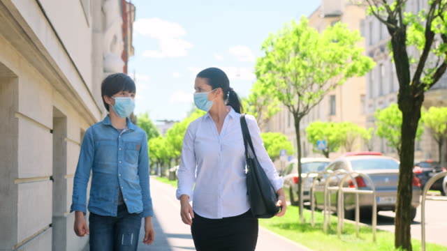 Mother and Young Son in Protective Masks Walking Outdoors video