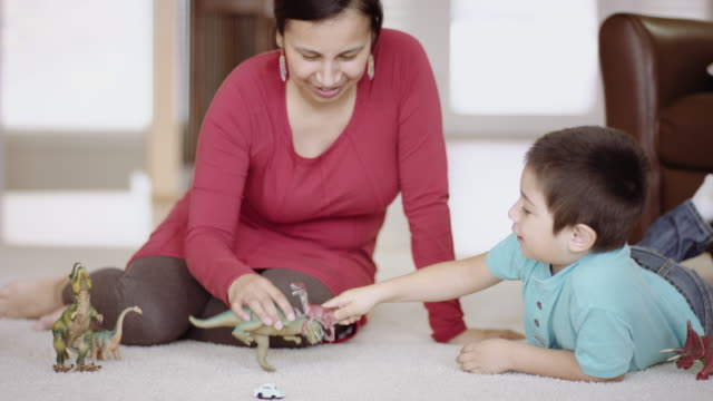 Mother and young son playing with dinosaurs Mother and young son playing with dinosaurs indian family stock videos & royalty-free footage