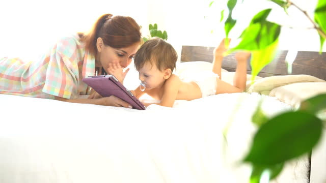 mother and young son to lie on the bed and use the Internet on the Tablet video