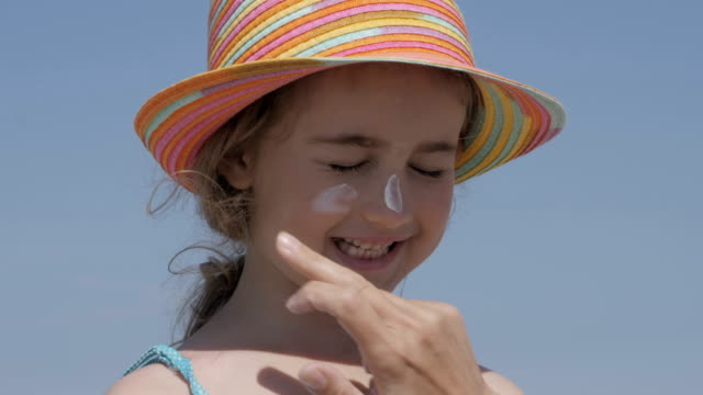 mother applying sunblock cream on daughter. young girl having sunscreen applied. portrait of beautiful little girl having fun on the sea, cute smiling in panama, sun protection cream. - sun cream stock videos & royalty-free footage