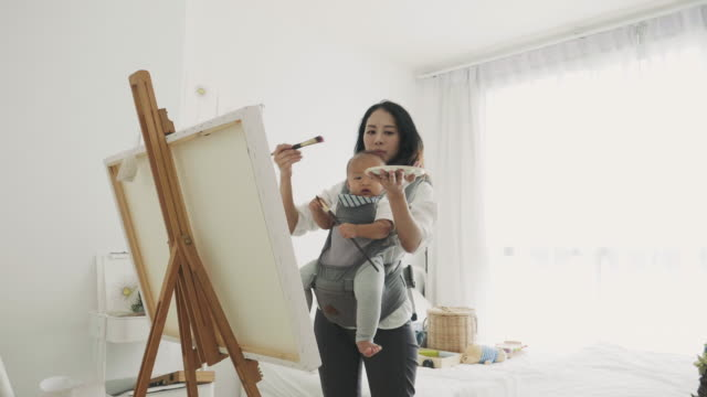 Mother artist painting picture while holding her son