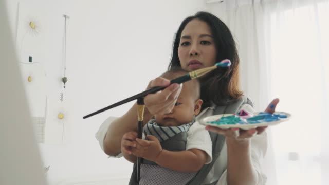 彼女の息子を押しながら絵を描いている母のアーティスト - マルチタスク点の映像素材/bロール
