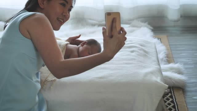 Mother Asian and newborn baby talking to each other through a video call n a smartphone