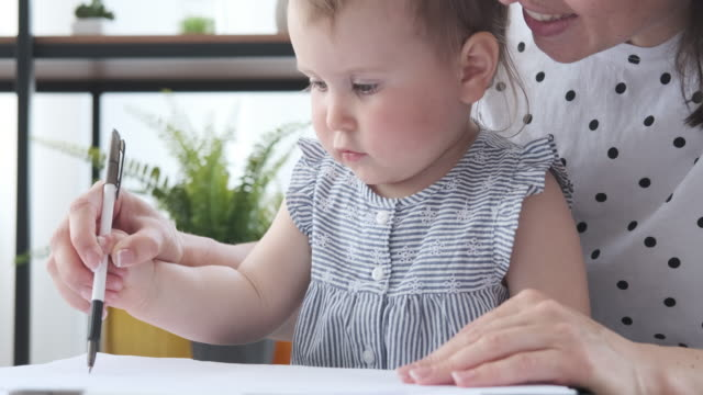 Mother assisting baby daughter to draw on paper