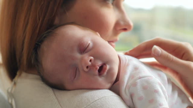 Mother At Home With Sleeping Newborn Baby Daughter video
