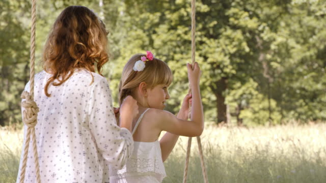 SLO MO Mother braiding daughter's hair on a swing video