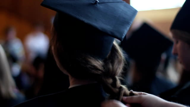 Mother braiding daughter's hair. Preparations for graduation ceremony at college video