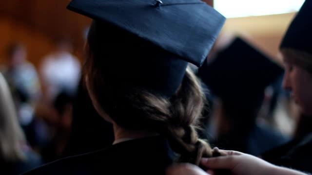Mère tresses fille cheveux. Préparation pour une cérémonie de remise des diplômes à l'université - Vidéo