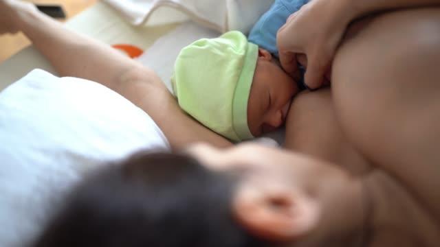 vidéos et rushes de mère l'allaitement un garçon nouveau-né - naissance