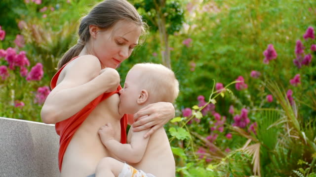 Mother breastfeeding her baby in nature outdoors