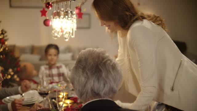 mother brings dinner to family sitting on christmas table - christmas gift family bildbanksvideor och videomaterial från bakom kulisserna