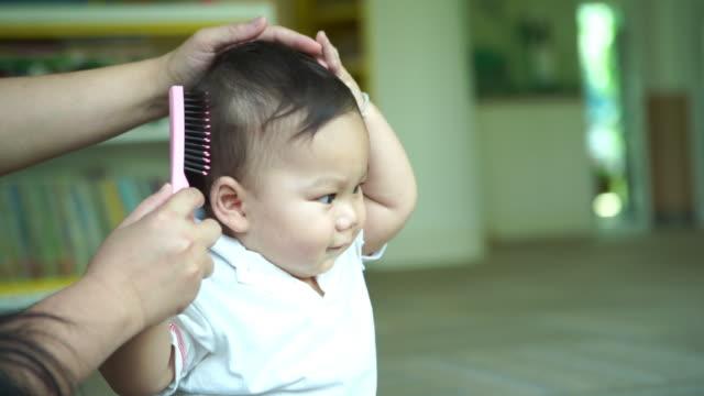 vidéos et rushes de mère brossant les cheveux sains pour le bébé - salons et coiffeurs