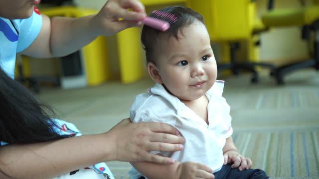 vidéos et rushes de mère brossant les cheveux sains pour bébé - salons et coiffeurs