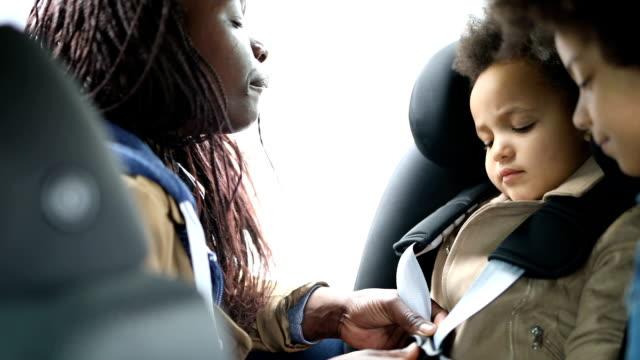 mor buckling hennes dotter i hennes bil barn stol - förberedelse bildbanksvideor och videomaterial från bakom kulisserna