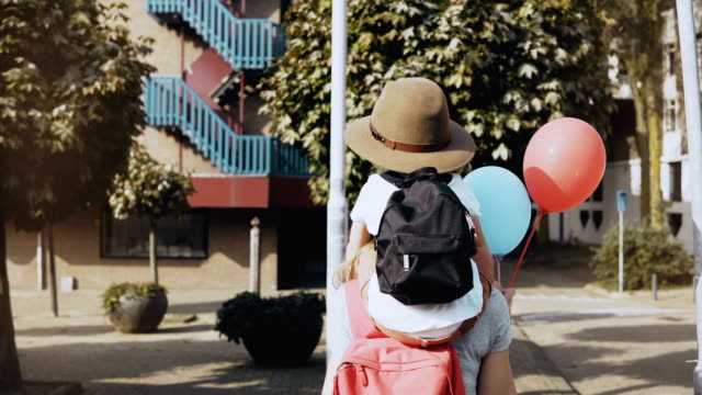 mother carries son on shoulders among houses. woman walking with a kid in hat and two air balloons. lifestyle 4k - viaggiare zaino in spalla video stock e b–roll
