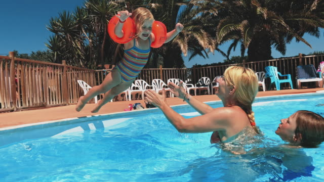 Mother catching girl jumping into swimming pool Mother catching her daughter jumping into swimming pool. Family enjoying summer vacations. They are at tourist resort. catching stock videos & royalty-free footage