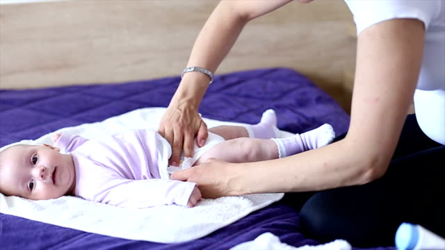 Mother changes the diaper of her daughter video