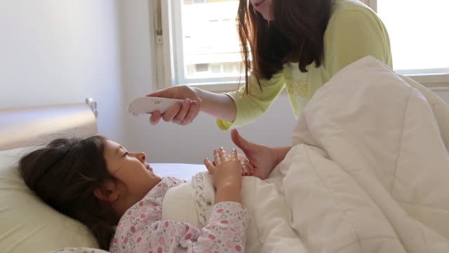 Mother checking daughter's body temperature with infrared thermometer Mother checking daughter's body temperature with infrared thermometer in bedroom at home double bed stock videos & royalty-free footage