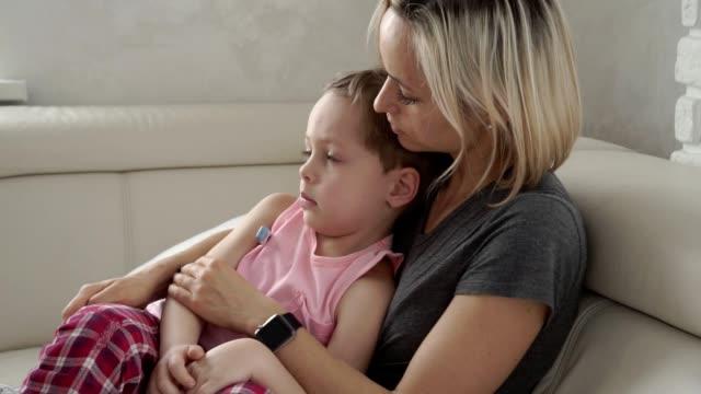 vídeos y material grabado en eventos de stock de madre de comprobación de temperatura de su hijo enfermo. niño enfermo con fiebre y enfermedad en la cama. - flu
