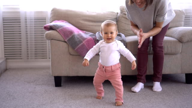 Mother clapping while baby girl is learning to walk video