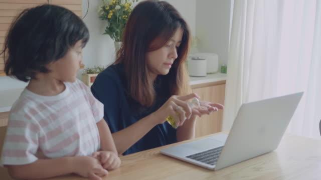 vidéos et rushes de la mère nettoyant les mains de son fils avec le désinfectant de main d'alcool protègent son enfant contre des virus - gel hydroalcoolique