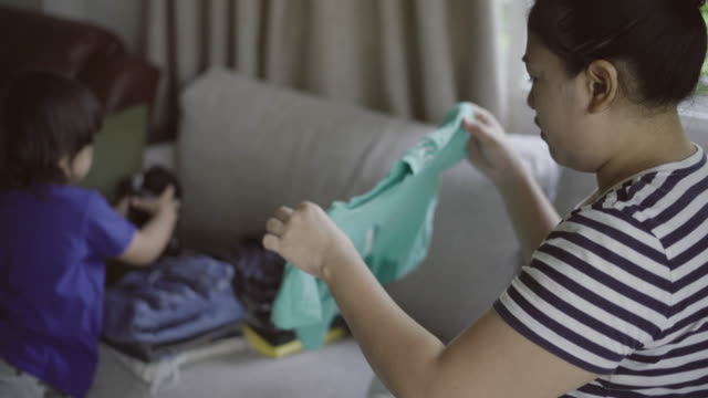 Mother collect clothes with boy video