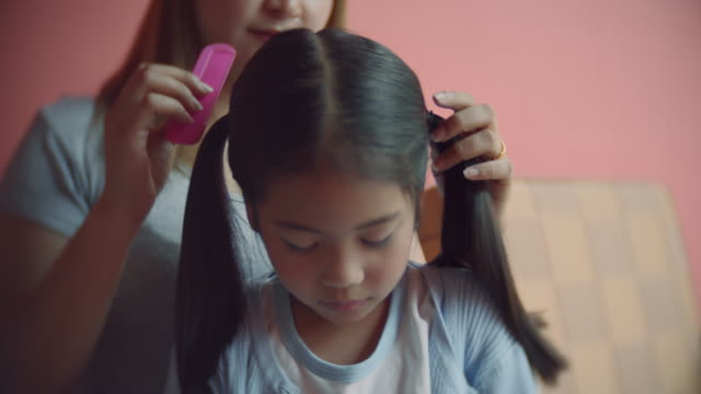 Mother combing the daughter's hair playing on the smart phone.Tilt down