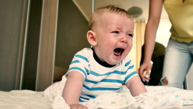 Mother comes to a crying baby to change his diaper video