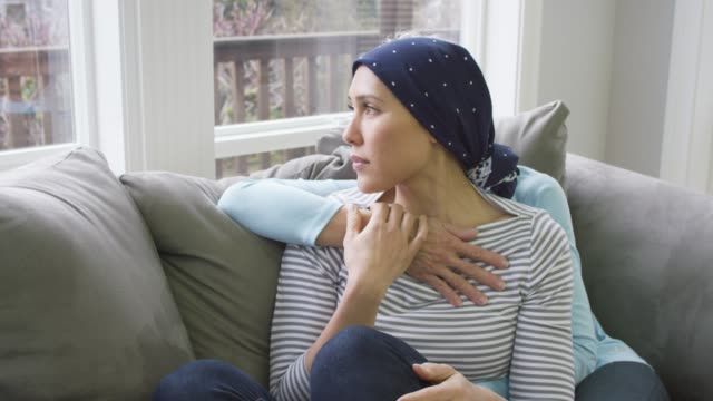Mother Comforting Her Daughter Who is Recovering from Cancer A mother sits on a couch with her arm around her adult daughter who is recovering from cancer and wearing a head scarf cancer patient stock videos & royalty-free footage