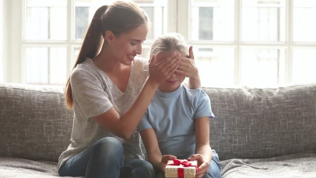 Mother cover eyes with hand daughter and presenting her gift