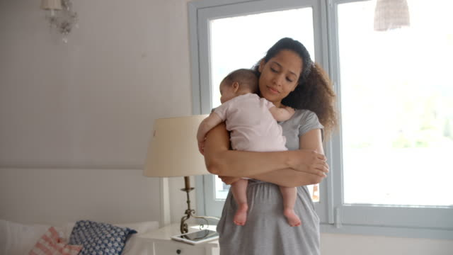 Mother Cuddling Baby Daughter At Home In Front Of Window video