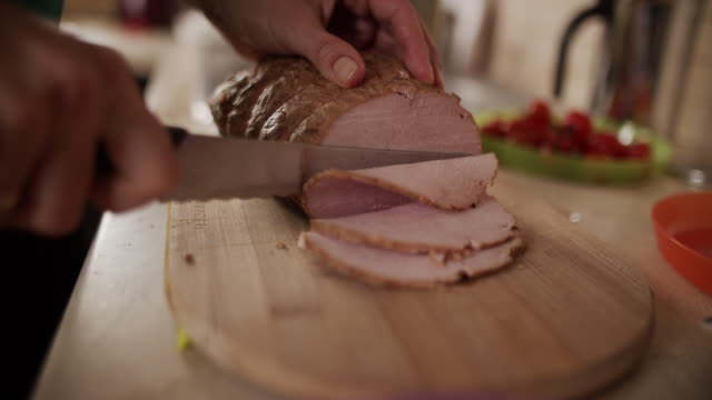 Mother cutting slices of ham for supper Mother is cutting slices of ham for supper  BMPCC4K, RAW Q0 pork stock videos & royalty-free footage